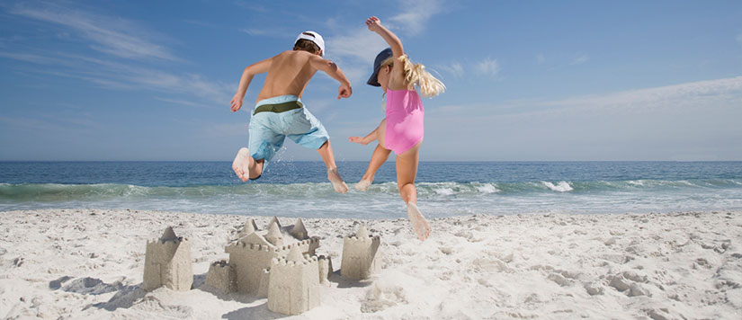 Kids jumping a over sandcastle
