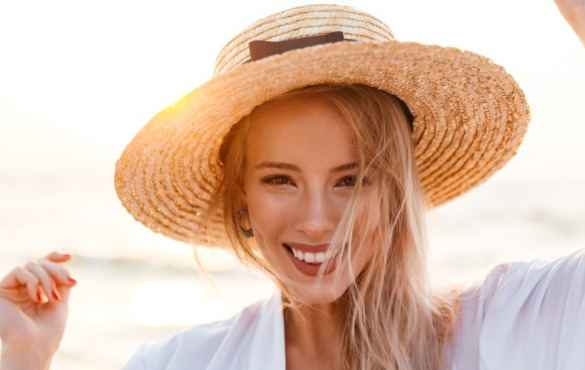 woman wearing hat on the beach | Williamson Realty