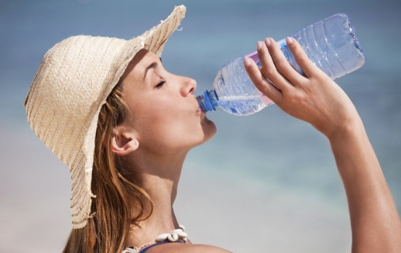 woman drinking water on the beach | Williamson Realty