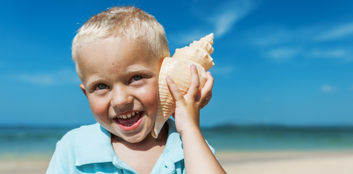 little boy listening to conch shell on the beach | Williamson Realty