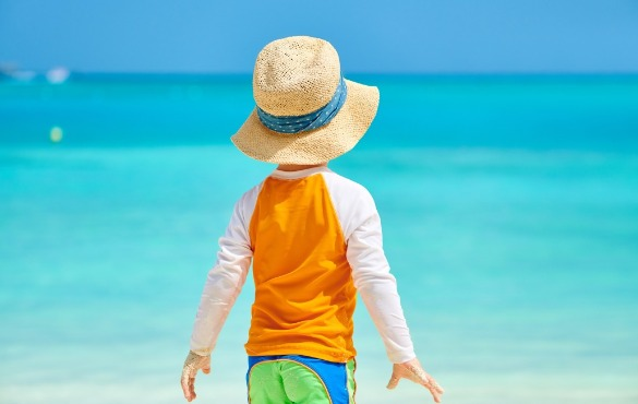 young boy wearing rash guard on the beach | Williamson Realty