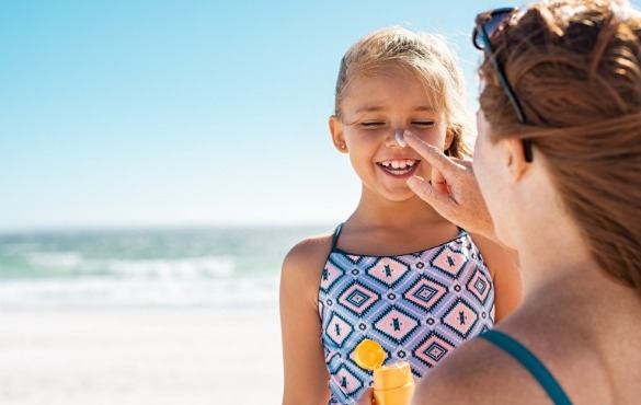 mother reapplying sunscreen to daughter on the beach | Williamson Realty
