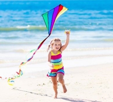 little girl flying a kite on the beach | Williamson Realty
