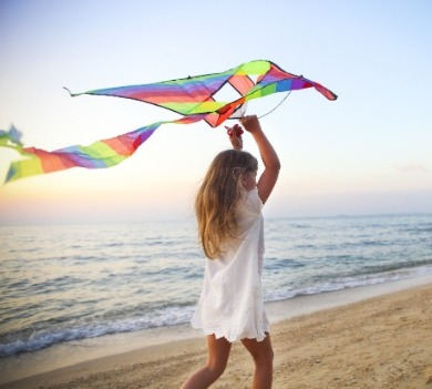 young girl on the beach with a kite | Williamson Realty