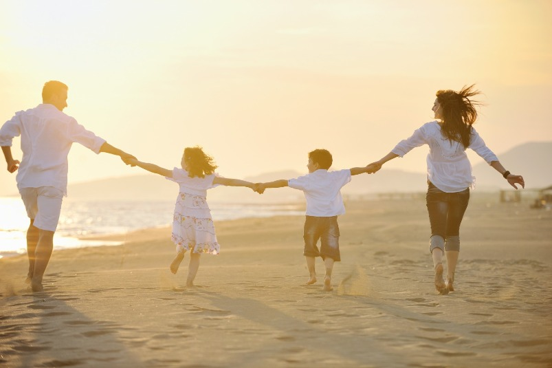 family walking on the beach | Williamson Realty