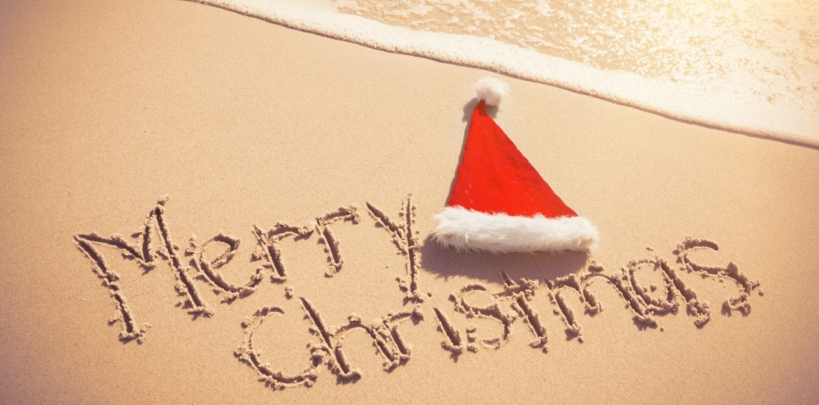 Merry Christmas written in sand with Santa Hat  | Williamson Realty