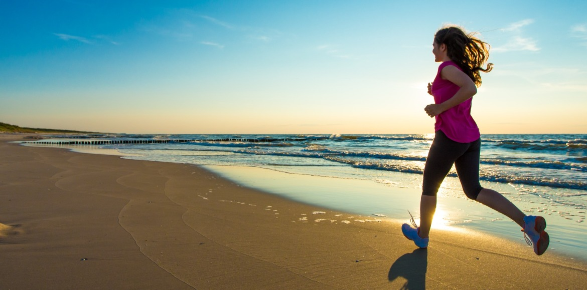 woman running on the beach | Williamson Realty