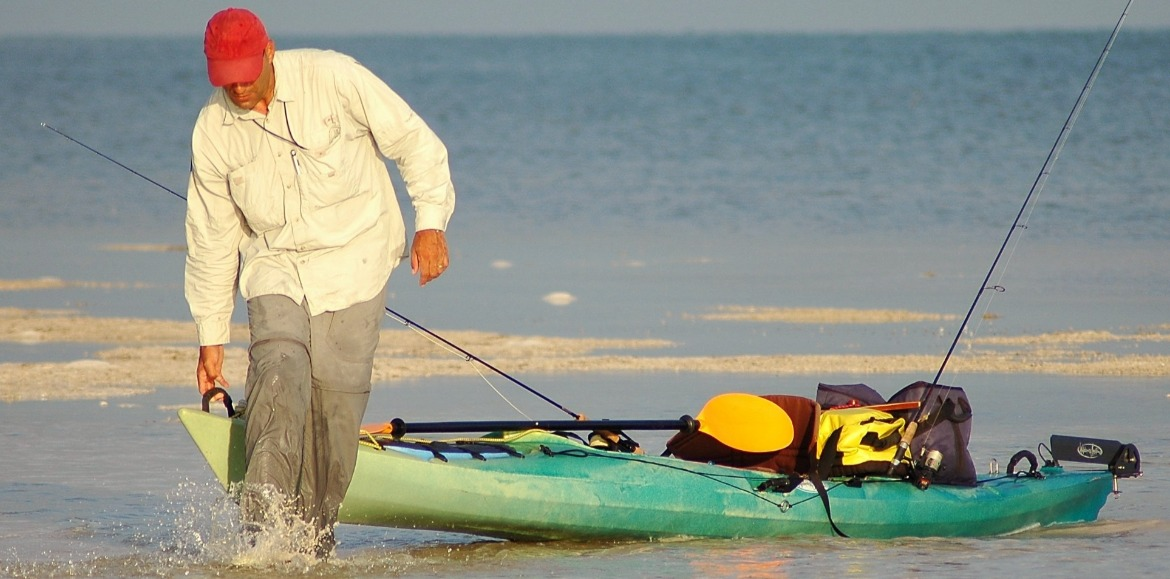 man pulling his fishing kayak out of the water on the beach | Williamson Realty
