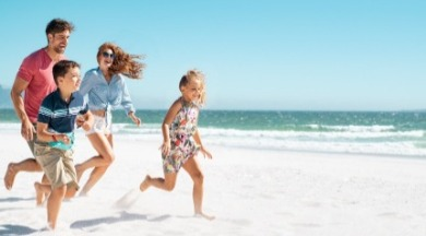 family happily running on the beach | Williamson Realty