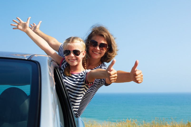 mom and daughter on beach thumbs up | Williamson Realty Vacations