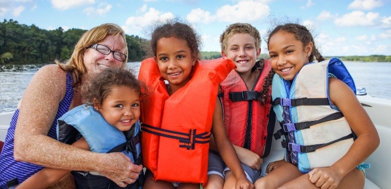 family wearing life jackets on a boat | Williamson Realty